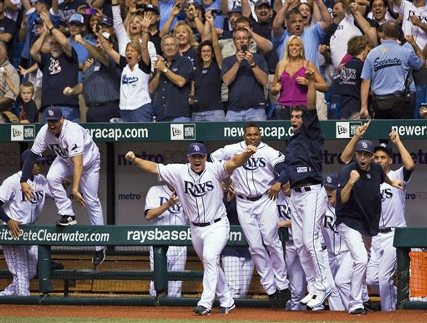 Tampa Bay Rays' Kelly Shoppach, right, and Matt Garza celebrate with fans after the Rays clinched a playoff berth with a 5-0 win over the Baltimore Orioles in a baseball game Tuesday, Sept. 28, 2010, in St. Petersburg, Fla. (AP Photo/Chris O'Meara)