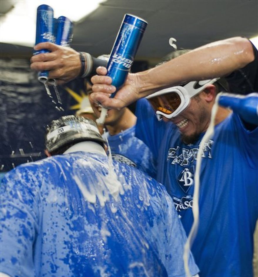 Tampa Bay Rays' Matt Garza, right, pours beer over Willy Aybar after the Rays beat the Baltimore Orioles 5-0 in a baseball game to clinch a playoff spot Tuesday, Sept. 28, 2010, in St. Petersburg, Fla. (AP Photo/Steve Nesius)