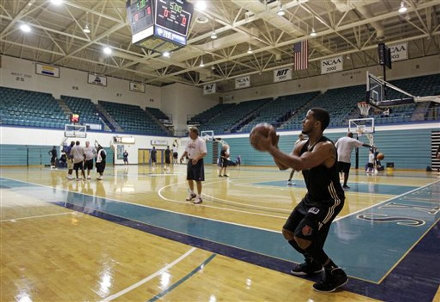 "Charlotte Bobcats' D.J. Augustin, left, listens to assistant coach Dave Hanners, right, during training camp for the NBA basketball team in Wilmington, N.C., Tuesday, Sept. 28, 2010.  The Bobcats nearly obtained Jose Calderon and then Devin Harris to replace Raymond Felton, but those deals fell through. That leaves D.J. Augustin as the front-runner to become Brown's point guard, a tall task with Brown saying he ""died"" when Felton left for New York. (AP Photo/Chuck Burton)"