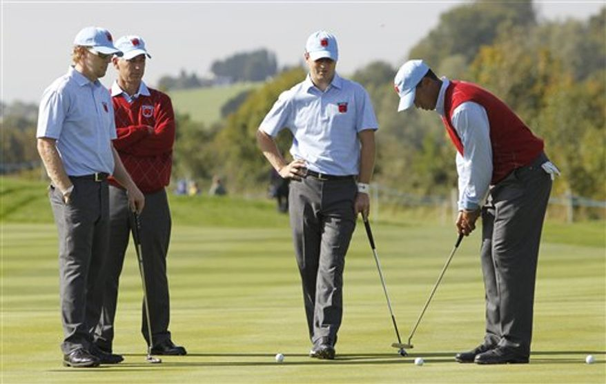 Tiger Woods, right, of the U.S. plays a shot as team members Hunter Mahan, left, Dustin Johnson, second right, and U.S. team captain Corey Pavin look on during a practice round at the 2010 Ryder Cup golf tournament in Newport, Wales, Tuesday, Sept.  28, 2010. The tournament starts Friday Oct. 1. (AP Photo/Jon Super)