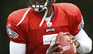 Philadelphia Eagles quarterback Michael Vick looks down field before passing a ball during practice at the team's NFL football training facility in Philadelphia, Wednesday, Sept. 29, 2010. (AP Photo/Matt Rourke)