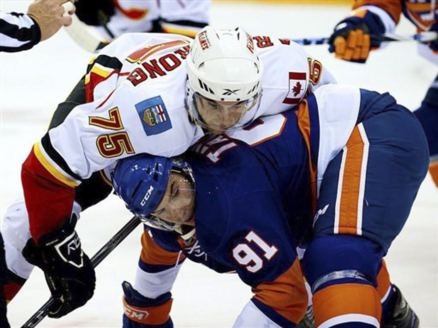 New York Islanders defensemen James Wisniewski rounds his net as Calgary Flames forward Greg Nemisz trails during the first period of a preseason NHL hockey game in Saskatoon, Saskatchewan, on Wednesday, Sept. 29, 2010. (AP Photo/The Canadian Press, Steve Hiscock)