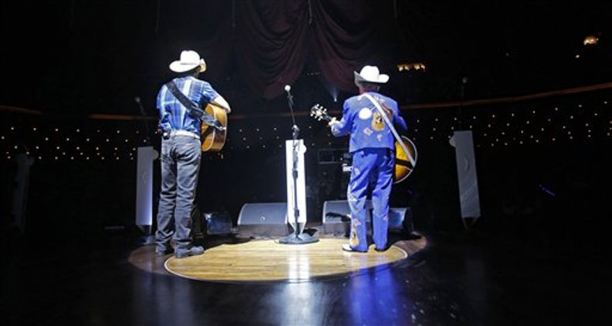 Country music stars Brad Paisley, left, and Little Jimmy Dickens, take the stage for the opening song as the curtain goes up in the Grand Ole Opry House on Tuesday, Sept. 28, 2010, in Nashville, Tenn. The show is the first to be held in the Opry House since the facility was heavily damaged by floodwaters in May. (AP Photo/Mark Humphrey)