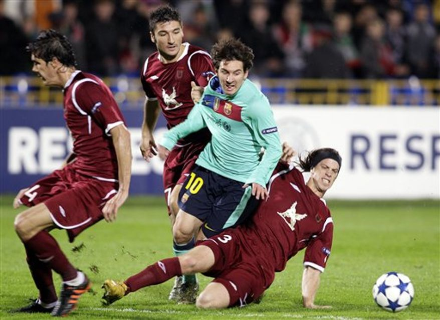 Barcelona's Lionel Messi, left, and Rubin Kazan's Christian Noboa struggle for the ball during their Champions League Group D soccer match in Kazan, Russia, Wednesday, Sept. 29, 2010. Game ended with a 1-1 draw. (AP Photo/Ivan Sekretarev)