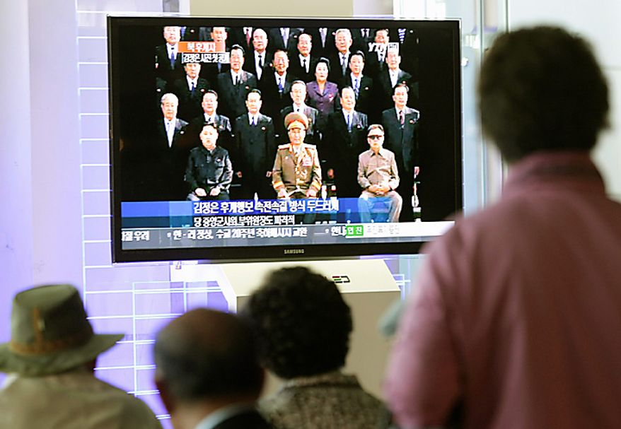 South Koreans watch a TV news program showing North Korean leader Kim Jong Il, right, posing for a group photo with newly elected members of the central leadership body of the Workers Party of Korea (WPK) including a man believed to be his third son Kim Jong Un, sitting at left of photo, and Vice Marshal Ri Yong Ho, sitting at center, as well as participants in the WPK Conference, in front of the Kumsusan Memorial Palace, in Pyongyang, North Korea, at the Seoul Railway Station in Seoul, South Korea, Thursday, Sept. 30, 2010. (AP Photo/Ahn Young-joon)