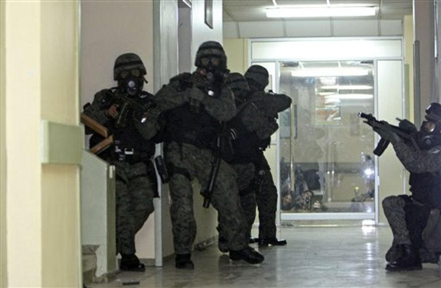Soldiers enter the police hospital where Ecuador's President Rafael Correa is being holed up by protesting police in Quito, Ecuador, Thursday Sept. 30, 2010.  The army rescued Correa from the hospital where he had been trapped by rebellious police for more than 12 hours while he was being treated for tear-gas fired by hundreds of police angry over a law that they claim would cut their benefits. (AP Photo/Dolores Ochoa)