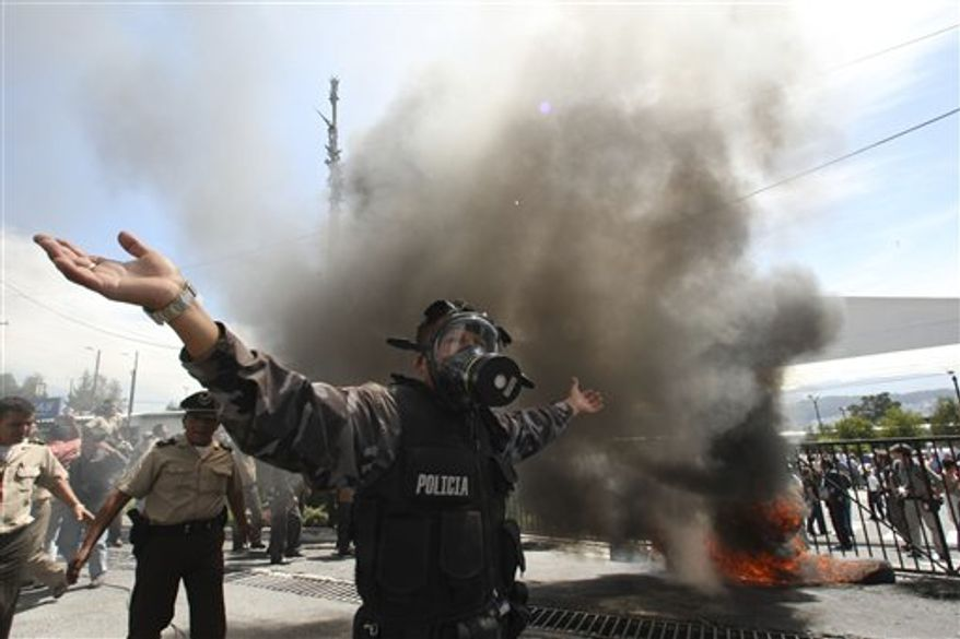 A police officer demonstrates next to a bonfire during a protest of police officers and soldiers against a new law that cuts their benefits at a police base in Quito, Ecuador, Thursday, Sept. 30, 2010. Hundreds of police protesting the new law plunged the country into chaos on Thursday, shutting down airports and blocking highways in a nationwide strike. (AP Photo/Dolores Ochoa)
