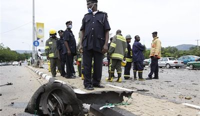 Nigerian police stand near wreckage after a car bomb exploded in Abuja, Nigeria, Friday, Oct. 1, 2010. Two car bombs blew up on Friday as Nigeria celebrated its 50th independence anniversary, killing a number of people in an unprecedented attack on the capital by suspected militants from the country's oil region. (AP Photo/Sunday Alamba)