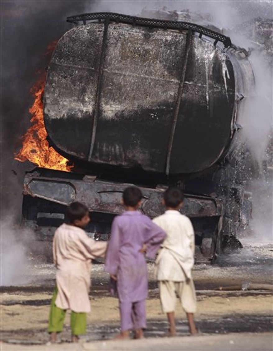 Pakistani boys talk beside still smoldering oil trucks in Shikarpur, southern Pakistan on Friday Oct. 1, 2010. Suspected militants set ablaze at least 27 tankers carrying fuel for U.S. and NATO troops in Afghanistan on Friday, police said. (AP Photo/Aaron Favila)