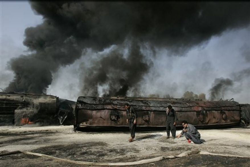 Pakistani police gather bullets littered around the still smoldering oil trucks in Shikarpur, southern Pakistan on Friday Oct. 1, 2010. Suspected militants set ablaze at least 27 tankers carrying fuel for U.S. and NATO troops in Afghanistan on Friday, police said. (AP Photo/Aaron Favila)