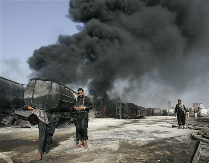 Pakistani police gather evidence beside still smoldering oil trucks in Shikarpur, southern Pakistan on Friday Oct. 1, 2010. Suspected militants set ablaze at least 27 tankers carrying fuel for U.S. and NATO troops in Afghanistan on Friday, police said. (AP Photo/Aaron Favila)