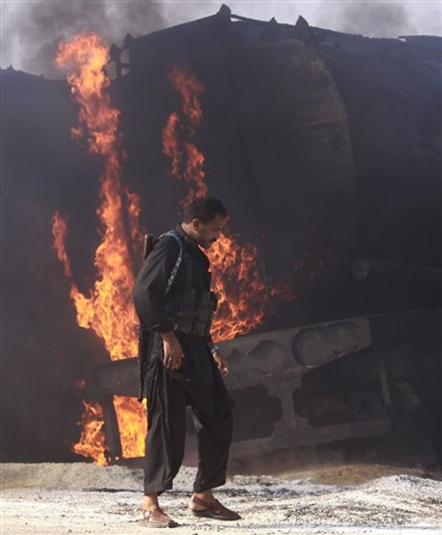 Pakistani police officer walks beside still smoldering oil trucks in Shikarpur, southern Pakistan on Friday Oct. 1, 2010. Suspected militants set ablaze at least 27 tankers carrying fuel for U.S. and NATO troops in Afghanistan on Friday, police said. (AP Photo/Aaron Favila)