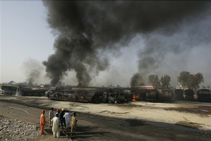 Pakistani firemen stand beside still smoldering oil trucks in Shikarpur, southern Pakistan on Friday Oct. 1, 2010. Suspected militants set ablaze at least 27 tankers carrying fuel for U.S. and NATO troops in Afghanistan on Friday, police said. (AP Photo/Aaron Favila)