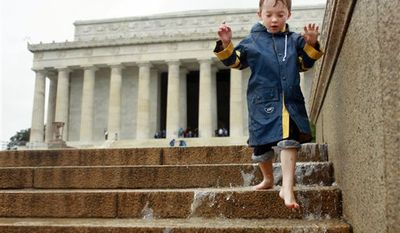 Joshua Pattel, 6, of Brisbane, Australia, plays in water flowing down the steps of the Lincoln Memorial in Washington, on Thursday, Sept. 30, 2010, during a heavy rain storm. (AP Photo/Jacquelyn Martin)