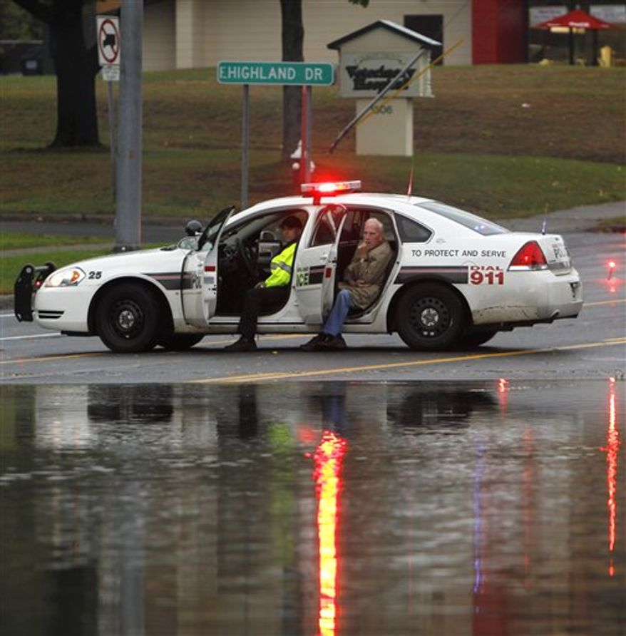 A man sits in a police vehicle after walking from his car that was stranded on a flooded road in Guilderland, N.Y., Friday, Oct. 1, 2010. (AP Photo/Mike Groll)