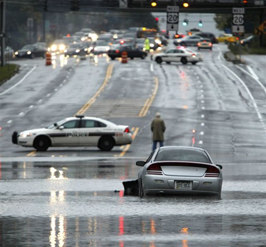 A vehicle is stranded on a flooded road in Guilderland, N.Y., Friday, Oct. 1, 2010. (AP Photo/Mike Groll)