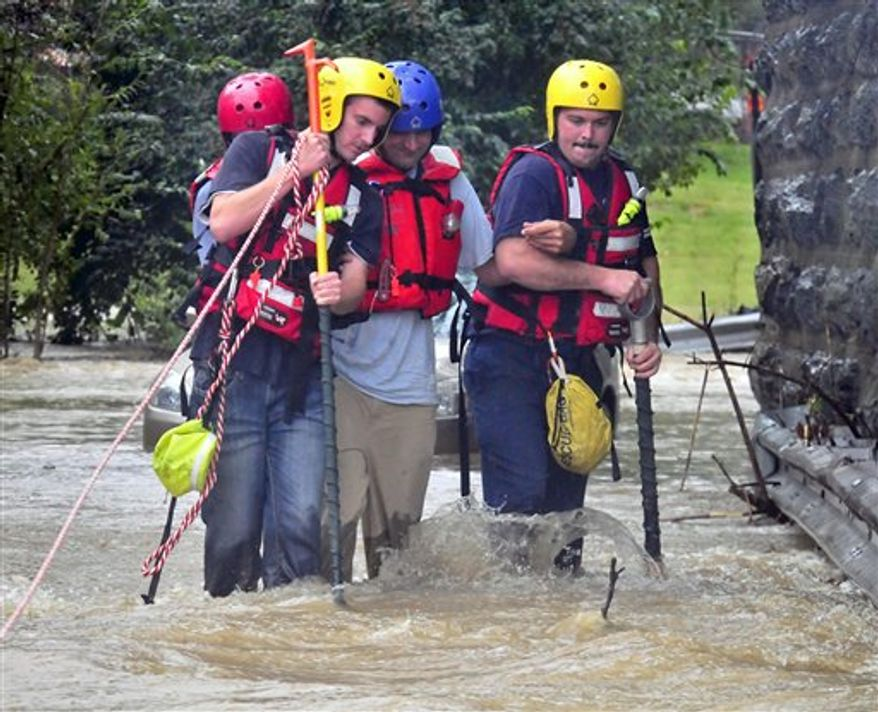 East Petersburg Fire Company firefighters walk a motorist through high water after his car became stranded in the Little Conestoga Creek, Thursday, Sept. 30, 2010 in Lancaster, Pa, Much of eastern Pennsylvania is under flood warnings as storms could bring as much as six inches of rain before leaving the area on Friday. The National Weather Service issued a tornado watch Thursday for counties stretching from Philadelphia west to York and north to Allentown. (AP Photo/Intelligencer Journal, Blaine Shahan)