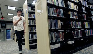 """Hiller Goodspeed walks by rows of books as he uses an iPod application called """"shake it"""" to find reading suggestions at the Orlando Public Library. People mistakenly think of libraries as old-fashioned, he says. (Associated Press)"""