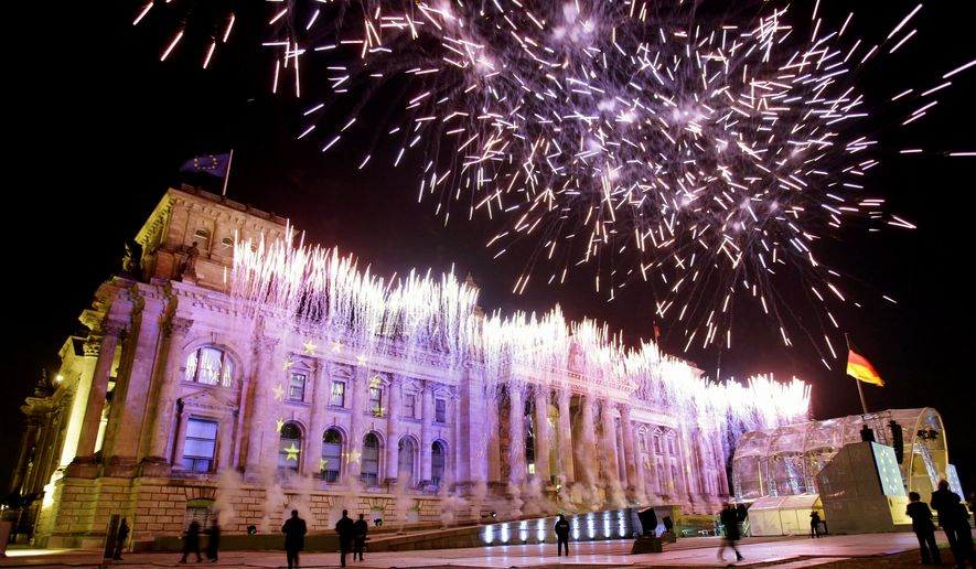 Fireworks illuminate the German Reichstag and the sky above in Berlin on Sunday during a reception marking the 20th anniversary of Germany's reunification. Germany's post-World War II division ended on Oct. 3, 1990, less than a year after the Berlin Wall fell. (Associated Press)
