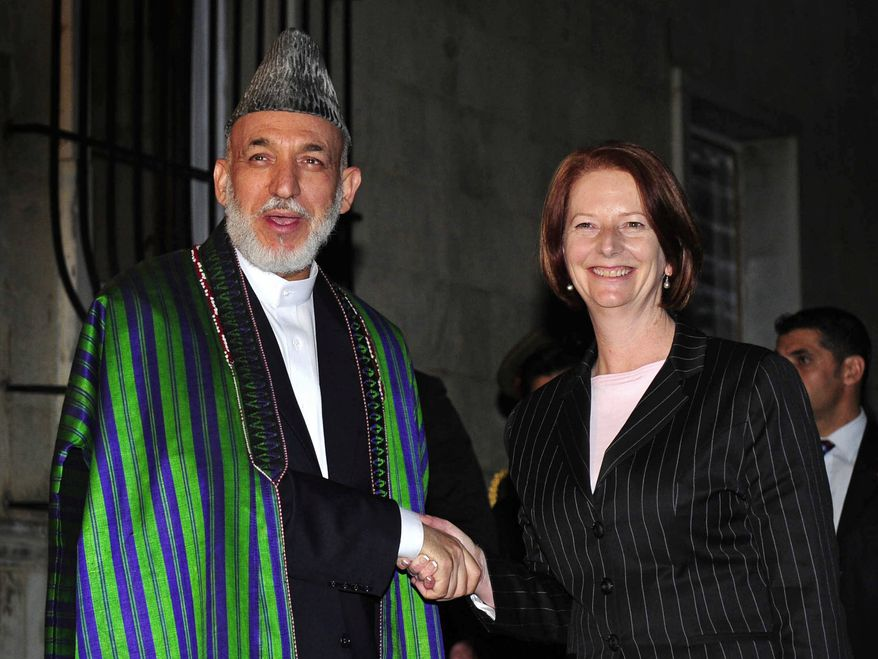 Australian Prime Minister Julia Gillard is welcomed by Afghan President Hamid Karzai during their first official meeting at the presidential palace in Kabul, Afghanistan, on Saturday, Oct. 2, 2010. Ms. Gillard pledged to continue supporting the U.S.-led mission there in her first overseas trip as Australia's leader. (AP Photo/Australian Department of Defense, Raymond Vance)