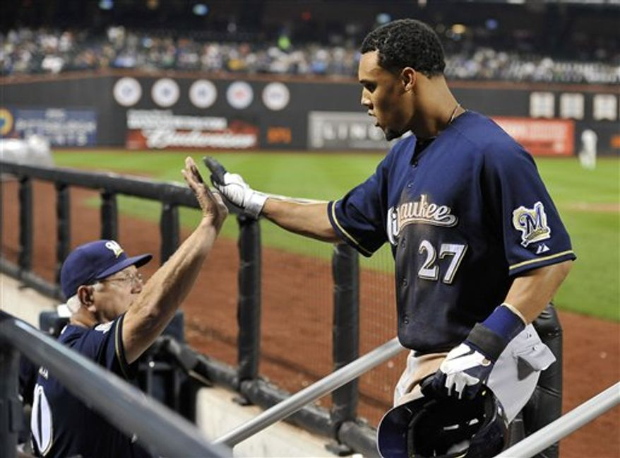 Milwaukee Brewers manager Ken Macha greets Carlos Gomez (27) at the dugout after Gomez scored the tying run on an RBI single by Corey Hart  in the eighth inning of the first game of a baseball doubleheader, Wednesday, Sept. 29, 2010, in New York. (AP Photo/Kathy Kmonicek)
