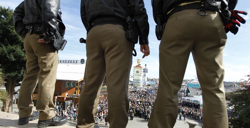 Police watch the crowd at the Oktoberfest in Munich on Sunday, Oct. 3, 2010. (AP Photo/Matthias Schrader)
