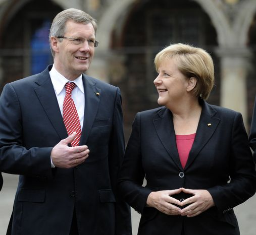 German President Christian Wulff (left) and Chancellor Angela Merkel stand in front of the Rathous, or town hall, in Bremen, Germany, before celebrations marking the 20th anniversary of Germany's reunification on Sunday, Oct. 3, 2010. (AP Photo/dapd/David Hecker)