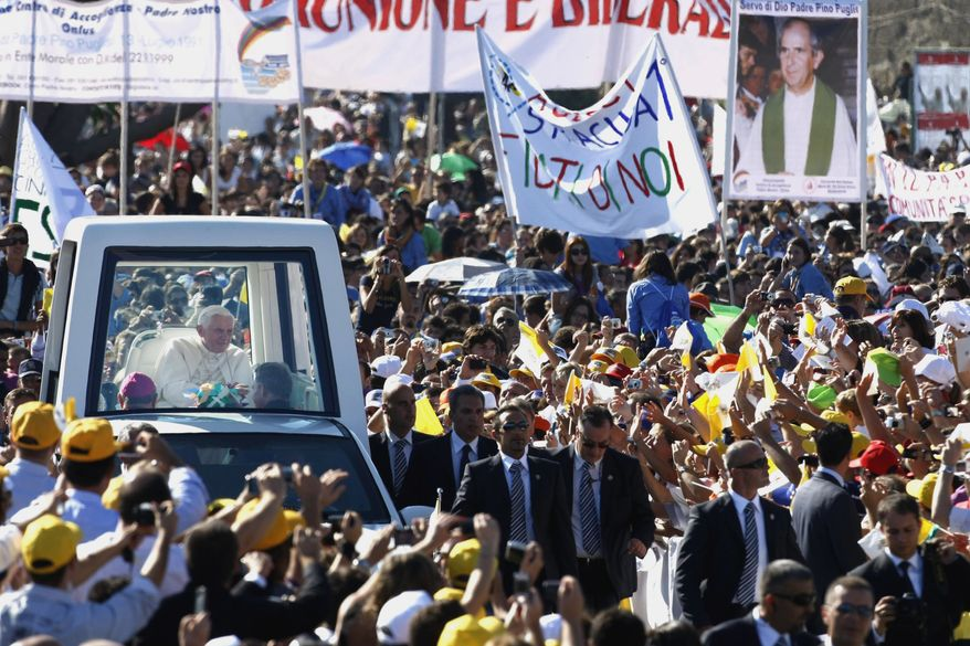 Pope Benedict XVI is greeted by faithful as he arrives by popemobile to celebrate an open-air Mass at Palermo, Sicily, on Sunday, Oct. 3, 2010. The pontiff paid tribute to a Palermo priest slain by the Mafia and encouraged Sicilians not to resign themselves to deep-rooted evil on the island, where organized crime has held sway for centuries. (AP Photo/Pier Paolo Cito)