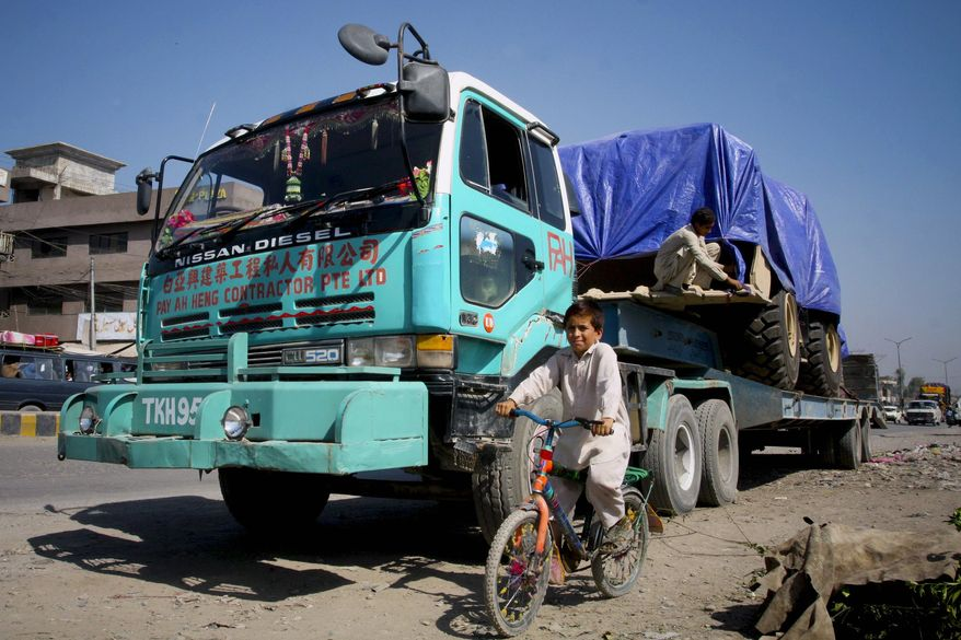 A Pakistani child bicycles past a parked truck carrying supplies for NATO forces in Peshawar, Pakistan, on Saturday, Oct. 2, 2010. Some 150 trucks were still waiting for Pakistan to reopen the border crossing at Torkham so they could deliver their supplies to Western troops in Afghanistan. (AP Photo/Mohammad Sajjad)