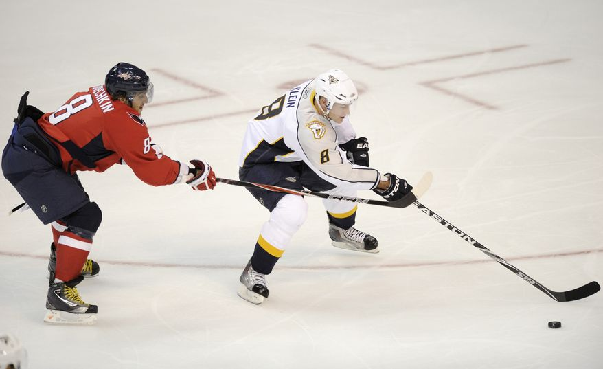 ASSOCIATED PRESS Washington Capitals left wing Alex Ovechkin, left, of Russia, chases after Nashville Predators defenseman Kevin Klein, right, during the second period of an NHL preseason hockey game, Sunday, Oct. 3, 2010, in Washington.