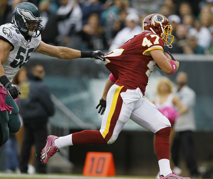 ASSOCIATED PRESS Philadelphia Eagles linebacker Stewart Bradley tries to hold on to Washington Redskins  tight end Chris Cooley as he scores a touchdown during the first half of an NFL football game in Philadelphia, Sunday, Oct. 3, 2010.