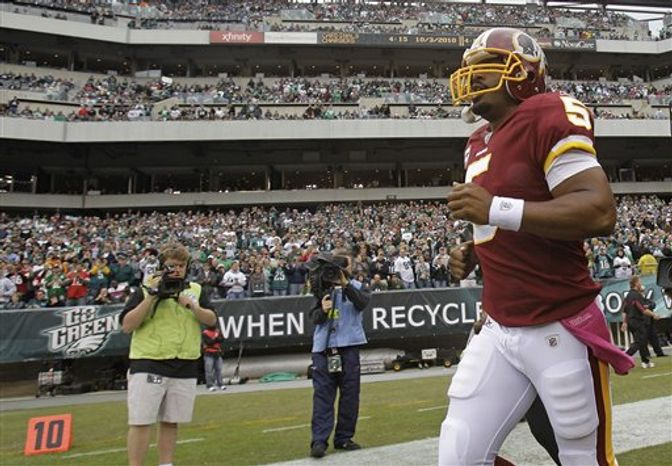 Philadelphia Eagles quarterback Michael Vick leans over after suffering an injury during the first half an NFL football game against the Washington Redskins in Philadelphia, Sunday, Oct. 3, 2010. (AP Photo/Matt Slocum)