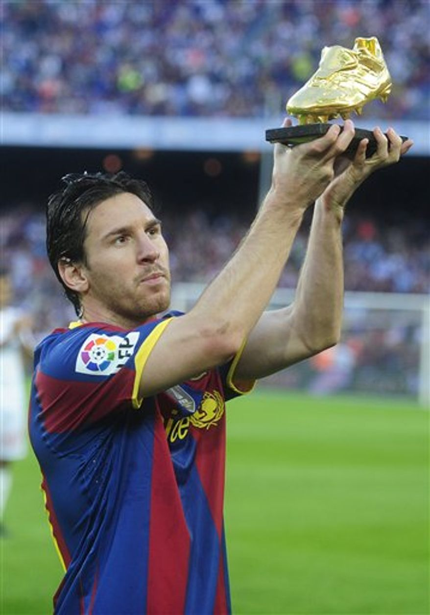 FC Barcelona's Lionel Messi shows the Bota de Oro (Golden Boot) trophy awarded to him as top scorer of all European Leagues before a match between FC Barcelona's and Mallorca  during a Spanish La Liga soccer match at the Camp Nou stadium in Barcelona, Spain, Sunday, Oct. 3, 2010. (AP Photo/Manu Fernandez)