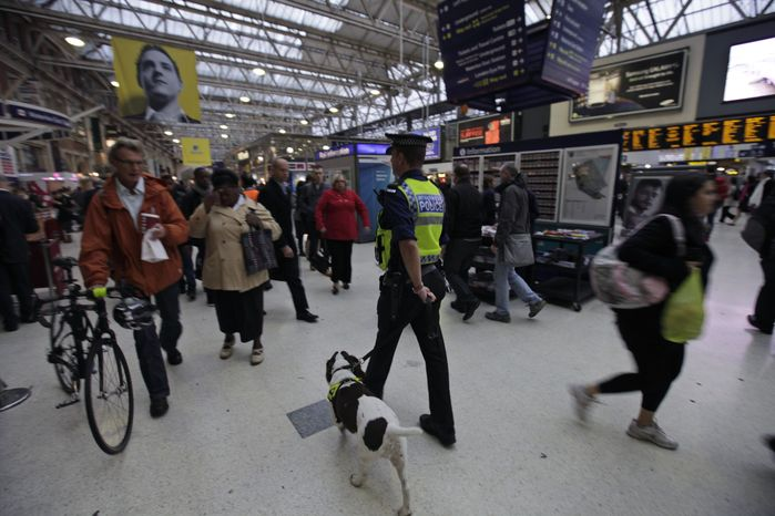 "A police officer with a dog patrols a central London train station on Monday, Oct. 4, 2010. Britain's Foreign Office has upgraded its travel advice for France and Germany, warning Britons going to those countries that the threat of terrorism there is high. British Home Secretary Theresa May said that the threat of terrorism in the United Kingdom remains unchanged at ""severe,"" meaning an attack is highly likely. (AP Photo/Lefteris Pitarakis)"