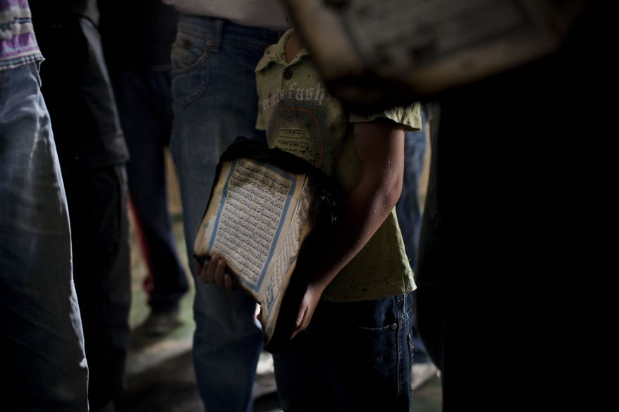 """A Palestinian child holds a charred Koran inside a mosque in the West Bank village of Beit Fajjar, near Bethlehem, on Monday, Oct. 4, 2010, after arsonists, scrawling """"Revenge"""" on a wall in Hebrew, torched the mosque. The blaze threatens to stoke new tensions over deadlocked Mideast peacemaking. (AP Photo/Bernat Armangue)"""