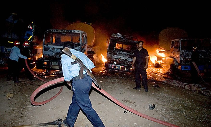 A Pakistani police officer, centre, helps Pakistani fire fighters to extinguish burning oil tankers after militants attacked a terminal in Rawalpindi, Pakistan, early Monday, Oct. 4, 2010.  Police say suspected militants have attacked and set on fire at least 20 oil tankers in Pakistan that were en route to NATO and US troops in Afghanistan. (AP Photo/Anjum Naveed)