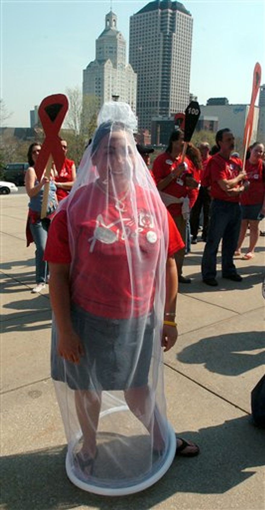 FILE - In this April 20, 2005 file photo, student Marissa Manzi wears a condom costume at an AIDS Awareness Day rally outside the state Capitol in Hartford, Conn. The male-female orgasm gap. The sex lives of 14-year-olds. An intriguing breakdown of condom usage rates, by age and ethnicity, with teens emerging as more safe-sex-conscious than boomers. That's just a tiny sampling of the data being unveiled Monday, Oct. 4, 2010 in what the researchers say is the largest, most comprehensive national survey of Americans' sexual behavior since 1994. (AP Photo/Bob Child, File)