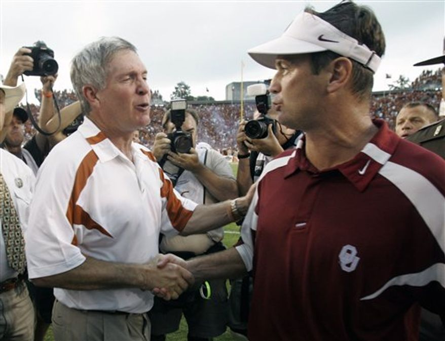 FILE - In this Oct. 6, 2007 file photo, Texas coach Mack Brown, left, congratulates Oklahoma coach Bob Stoops after Oklahoma beat Texas 28-21 in an NCAA college football game in Dallas. The Red River rivals will meet again on Saturday. (AP Photo/L.M. Otero, File)