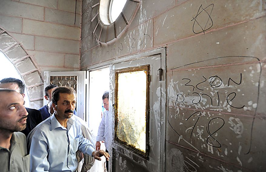 Palestinians look at Hebrew graffiti, that reads 'Mosque toilet 18', with a Star of David in the torched and vandalized Prophet's Mosque in Beit Fajjar, north of Hebron in the West Bank, October 4, 2010, 2010.  Palestinian sources said that Jewish settlers entered the mosque and torched the mosque, Koran books, prayer rugs and left Hebrew graffiti with slogans against Arabs, Muslims and Mohammad on the walls.  UPI/Debbie Hill