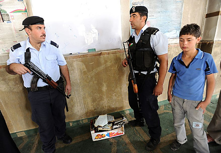 Palestinian police stand by a box of burned Koran books in the torched and vandalized Prophet's Mosque in Beit Fajjar, north of Hebron in the West Bank, October 4, 2010, 2010.  Palestinian sources said that Jewish settlers entered the mosque and torched the mosque, Koran books, prayer rugs and left Hebrew graffiti with slogans against Arabs, Muslims and Mohammad on the walls.  UPI/Debbie Hill