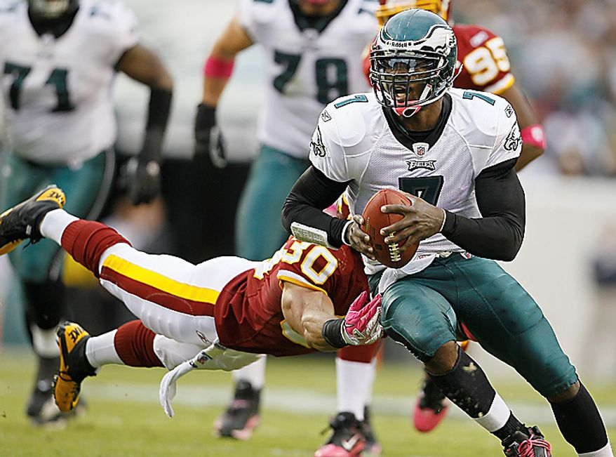 Washington Redskins safety LaRon Landry stretches to reach Philadelphia Eagles quarterback Michael Vick during the first half of an NFL football game in Philadelphia, Sunday, Oct. 3, 2010. Vick was injured on the play. (AP Photo/Matt Slocum)
