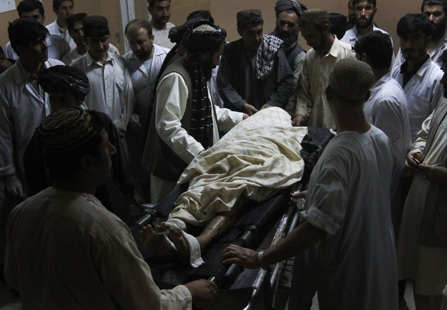 A man killed in a blast is surrounded by his relatives in a hospital in Kandahar city, south of Kabul, Afghanistan, Tuesday, Oct. 5, 2010. Two explosions rocked Kandahar on Tuesday where U.S. and Afghan forces are ramping up operations in areas long held by the Taliban. (AP Photo/Allauddin Khan)