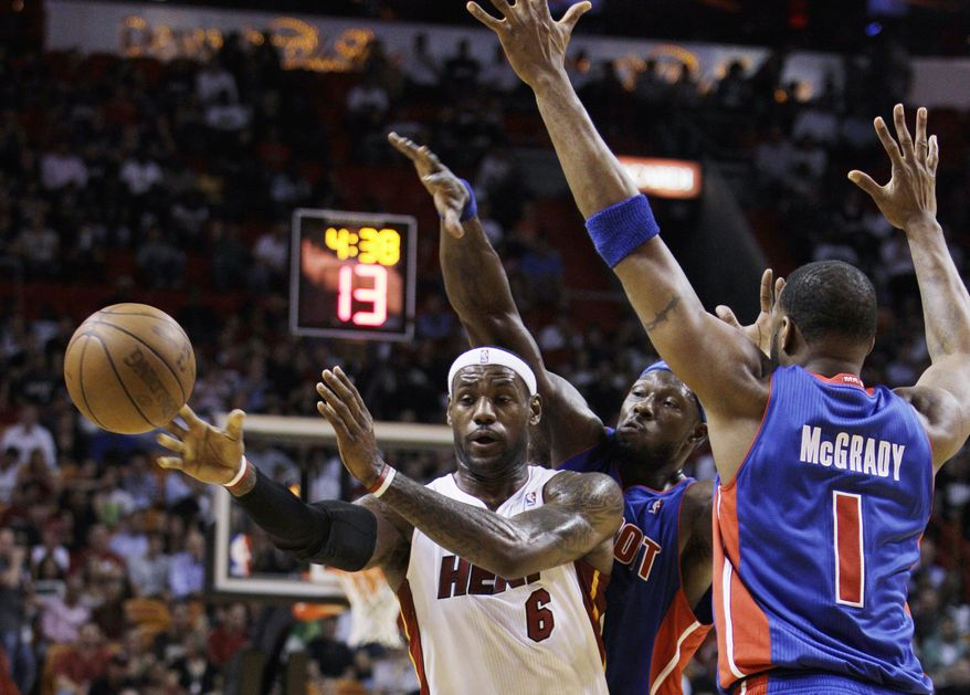 ASSOCIATED PRESS Miami Heat forward LeBron James passes away from Detroit Pistons center Ben Wallace, rear, and guard Tracy McGrady (1) during the first quarter of a preseason NBA basketball game Tuesday, Oct. 5, 2010, in Miami.