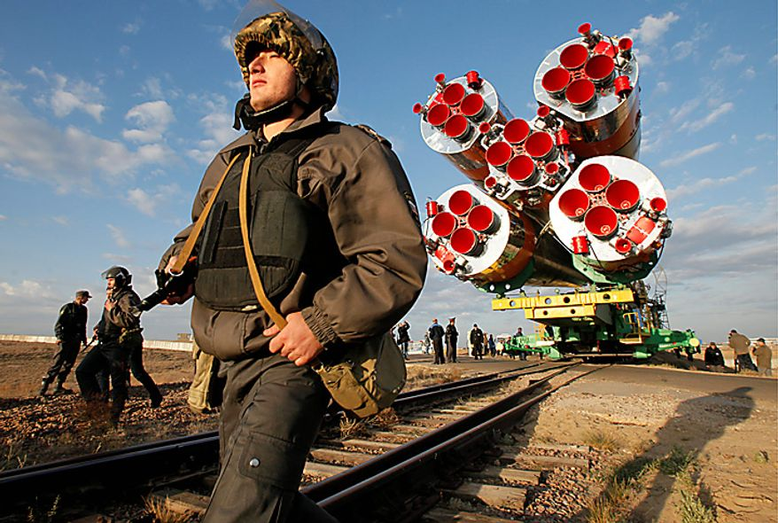 Russian police officers guard the Russian Soyuz TMA-01M space ship that will carry new crew to the international space station transported from hangar to the launch pad at the Russian leased Baikonur cosmodrome, Kazakhstan, Tuesday, Oct. 5, 2010. Start of the new Soyuz mission is scheduled on Friday, Oct. 8. (AP Photo/Dmitry Lovetsky)
