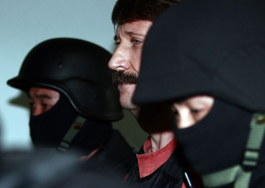 Suspected Russian arms smuggler Viktor Bout, center, is led by armed Thai police commandoes as he arrives at the criminal court in Bangkok Tuesday, Oct. 5, 2010.  (AP Photo/Apichart Weerawong)