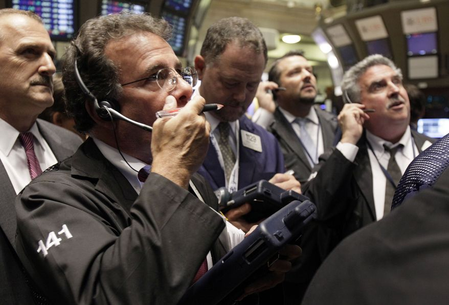 In this Sept. 30, 2010, photo, traders gather at a post on the floor of the New York Stock Exchange, in New York. U.S. stock futures are rising Tuesday, Oct. 5, 2010, following world markets higher after the central bank of Japan moved to weaken the yen.(AP Photo/Richard Drew)