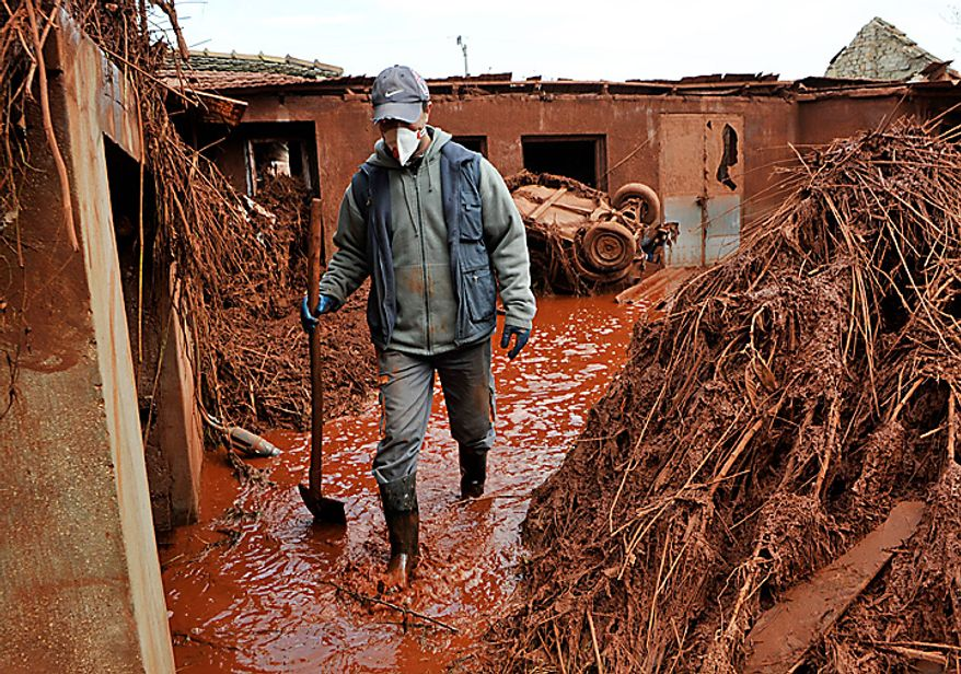 A villager walks through his yard flooded by toxic mud in the Kolontar, Hungary, Tuesday, Oct. 5, 2010. A third person has died in flooding caused by the rupture of a red sludge reservoir at an alumina plant in western Hungary, rescue services said Tuesday. Six people were missing and 120 injured in what officials said was an ecological disaster. The government declared a state of emergency in three counties affected by the flooding.  (AP Photo/Bela Szandelszky)