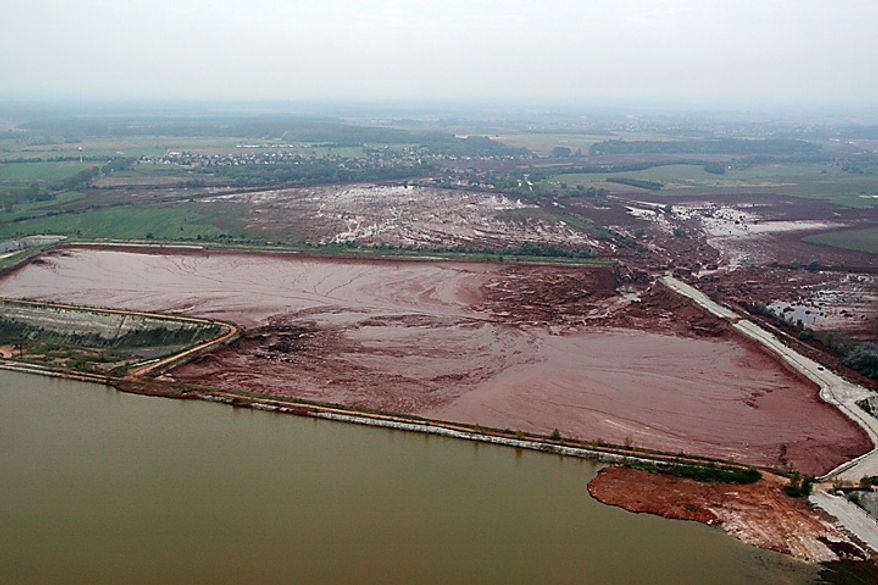 An aerial view of the broken dike, center right, of a reservoir containing red mud of an alumina factory near Ajka, 156 kms southwest of Budapest, Hungary, Tuesday, Oct. 5, 2010. The dike broke on Monday, and over one million cubic meters of the poisonous chemical sludge inundated three villages. The flood of toxic mud killed killed a yet unknown number of people, injured more than one hundred, with some people still missing. (AP Photo/MTI, Gyoergy Varga)