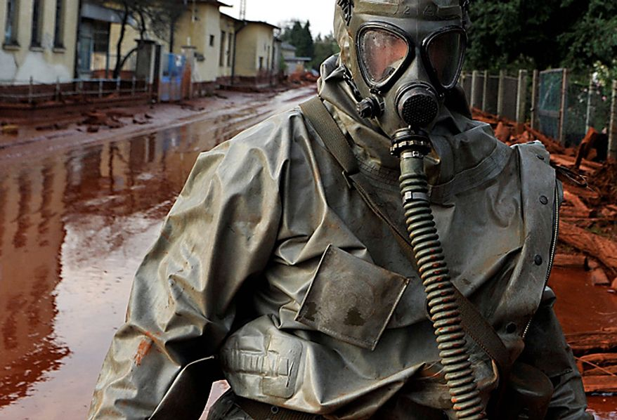 A Hungarian soldier wearing a chemical protection gear walks through a street flooded by toxic in the town of Devecser, Hungary, Tuesday, Oct. 5, 2010. Monday's flooding was caused by the rupture of a red sludge reservoir at an alumina plant in western Hungary and has affected seven towns near the Ajkai Timfoldgyar plant in the town of Ajka, 100 miles (160 kilometers) southwest of Budapest. (AP Photo/Bela Szandelszky)