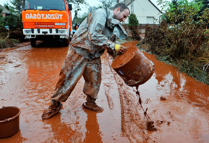 A Hungarian man cleans his yard after it was flooded by toxic mud in Devecser, Hungary, on Wednesday. Monday's flooding was caused by the rupture of a red sludge reservoir at a metals plant in Western Hungary and has affected seven towns near Ajka, 100 miles southwest of Budapest. The flood of toxic mud killed at least four people and injured more than one hundred. (Associated Press)
